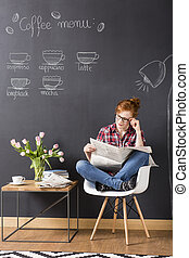 Morning press review - Shot of a young woman reading a...