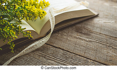 Morning relaxation and cozy with Solidago small yellow flower and white lace on the book with copy space for woman lifestyle , nostalgic concept