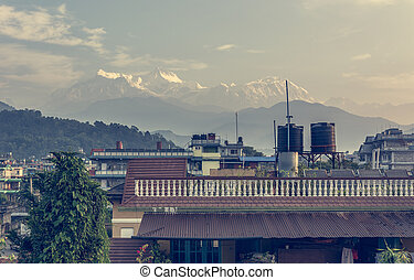 Morning rooftop view of mountains rising in distance.