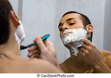 morning routine: a man shaving before going to work