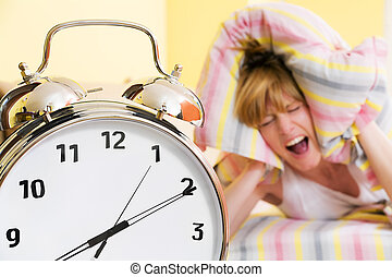 Close up of alarm clock. Young woman in the background covering ears with pillow.