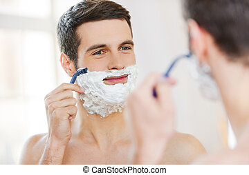 Morning routine. Handsome shirtless young man shaving his face and smiling while standing in front of the mirror