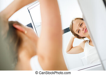 Morning stretch - Pretty, young woman in front of the mirror in the bathroom on an early morning