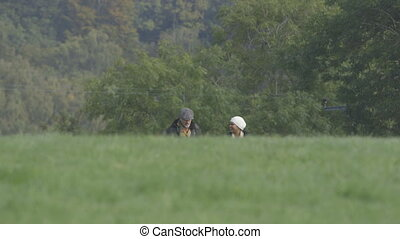 Morning stroll with the dog - Couple walking across a field,...
