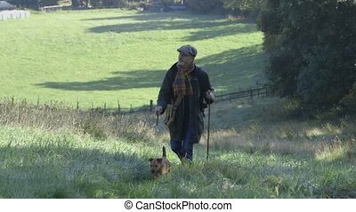 Morning stroll with the dog - Man walking his dog up a hill...