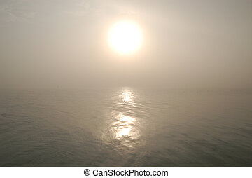 The morning sun and its reflection shine through the fog over Lake Erie.