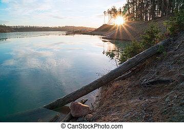 Morning sun on the shore of a sand quarry. Leningrad region.