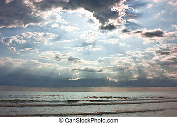 cloudy sky over the sea - morning sun rays through clouds -...
