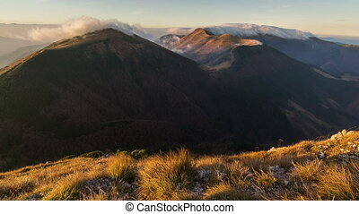 Morning sunlight in mountains with clouds flying over ridge time lapse in autumn