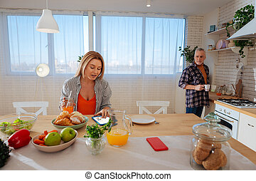 Blonde wife sitting at the table in kitchen talking to her husband