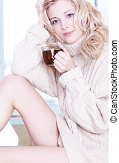 portrait of beautiful blonde girl in pullover drinking tea in the morning