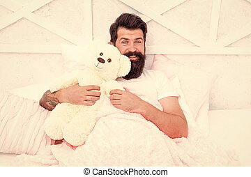 Morning vibes. happy wake up in the morning. good morning mood. time go to sleep. spend weekend in bed. feel comfortable at home. lazy man relax in bedroom. happy hipster with favorite bear toy