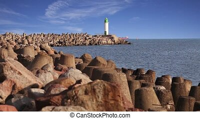 Morning view of lighthouse, sea and concrete breakwater in...
