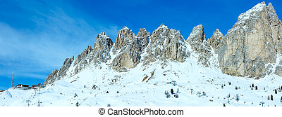 Morning winter rocky mountain panorama with ski station. Gardena Pass in Dolomites of South Tyrol in northeast Italy. All people are unrecognizable.