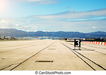 Morning with down sun lights at the runway of Gibraltar airport, mountains and Algeciras port at the background.