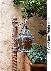 close-up of a Moroccan lantern outside a stucco house