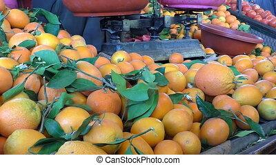 Moroccan market weighing oranges - Fruit seller weighing...