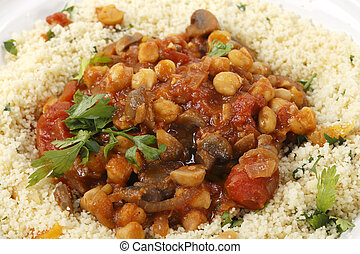 Chickpeas or garbanzo beans and quartered button mushrooms cooked in a spicy tomato and onion sauce and served with couscous mixed with parsley and refreshed dried apricots, Moroccan style, served in a tagine bowl