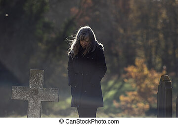 Mortality. Living with grief. Lady mourns at old cemetery...