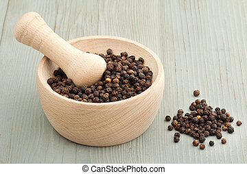 mortar and pestle with balck pepper on wooden board