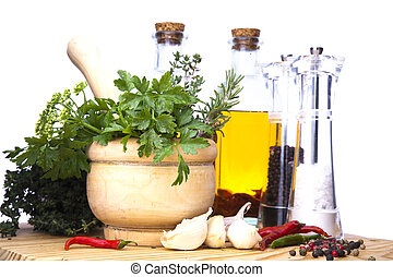 Mortar and pestle with fresh herbs, spices, virgin olive...