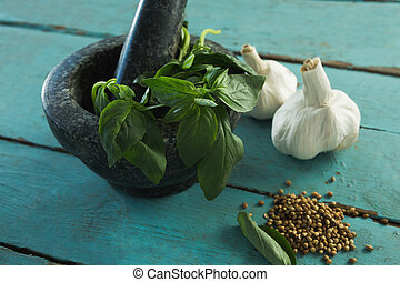 Mortar and pestle with herbs and spices on wooden table