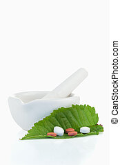 Mortar and pestle with pills on a leaf