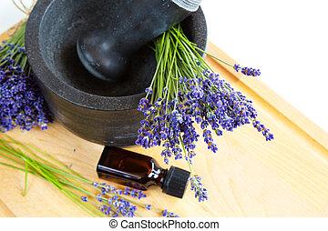 Mortar with lavender flowers, bottle of oil, herbal medicine