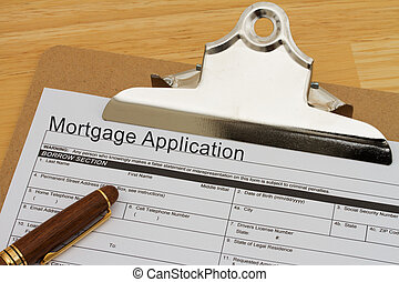 Mortgage Application Form on a clipboard with a pen on a...