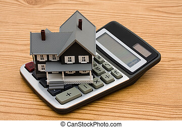 Mortgage Calculator - A model house on a calculator sitting...