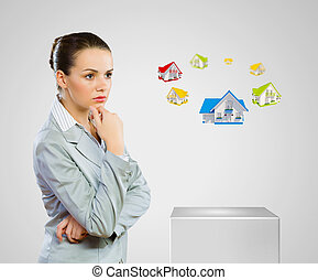Mortgage concept - Image of young woman in suit looking at...
