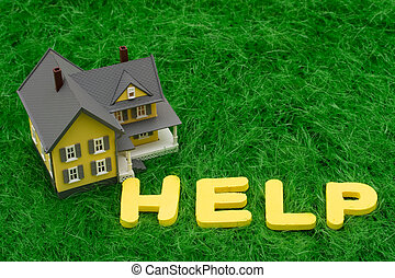House with the word help on grass. mortgage crisis