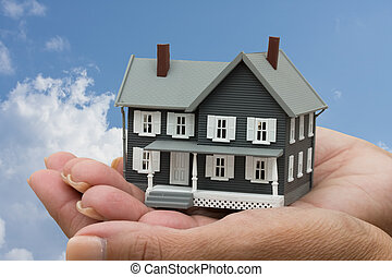 Mortgage Help - A model house sitting in hands on a sky...