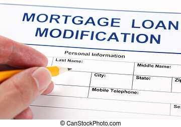 Mortgage Loan Modification application form and human hand with pencil.