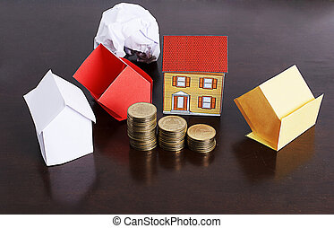 Mortgage loans concept with paper house and coins stack on wooden table