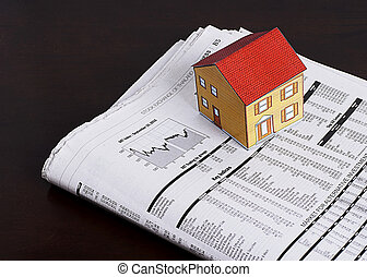 Mortgage loans concept with paper house and news paper on wooden table