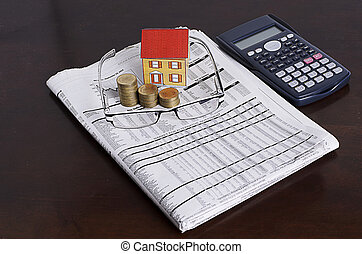 Mortgage loans concept with Paper house with coins stack, eyeglasses and news paper, calculator