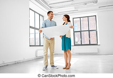happy couple with blueprint at new home