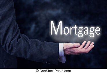 Mortgage - A businessmans hand holding the word, Mortgage.