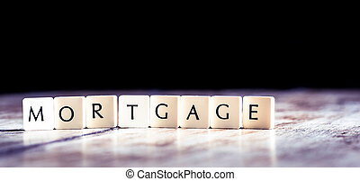 Mortgage word made of tiles on dark wooden background