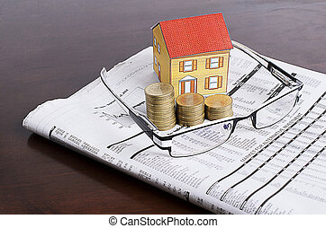 Mortgaget loans concept with coins stack with eye glasses and paper house on news paper