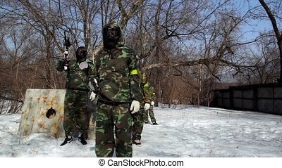 Several paintball players run to both sides and take...