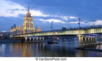Novoarbatsky bridge lit by lanterns in front of hotel...