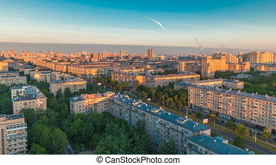 Moscow city bathed in yellow sun at dawn timelapse. An early foggy morning. Shadows moving on houses. Megalopolis aerial view from rooftop.
