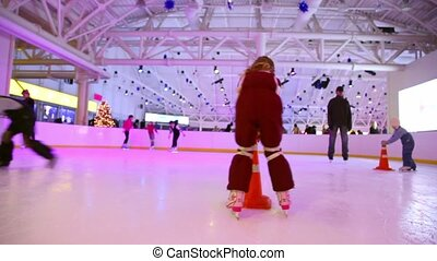 Little girl skates on ice rink in shopping center European