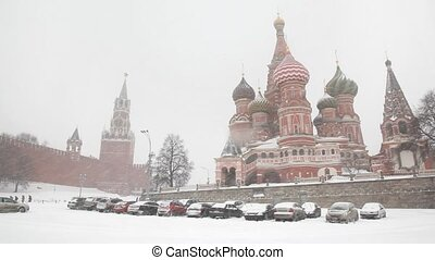 Moscow Kremlin's Spasskaya Tower and Saint Basil's Cathedral under snowfall