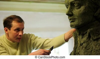 Sculptor Denis Petrov corrects unfinished A.Suvorov bust with knife and watch on it