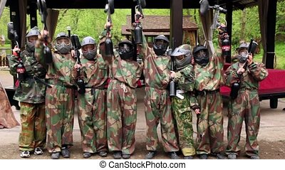 Eight teenagers paintball team stand and aim weapon to...