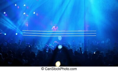 Popular Dutch DJ Armin Van Buuren on stage with blue...