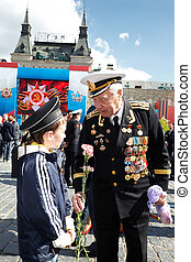 MOSCOW - MAY 9: World War II veteran of Navy in uniform with  carnations in the hand talks with boy in the peakless cap on Red Square on Victory Day, May 9, 2011, Moscow, Russia.